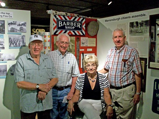 Gathering recently in the Warrensburg Museum of Local History around Joe DeMatties' barber chair are his offspring (seated): Allison Drake of Warrensburg, (standing, left to right): Joe Dematties of Queensbury, Ernie DeMatties of Poultney, Vt., Irving DeMatties of Queensbury. (Not pictured): Darlynn Bates  and Murray DeMatties.