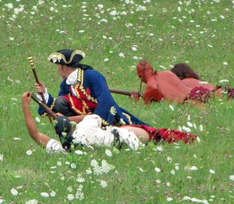 Jon Soule from Vermont is seen portraying a French officer pausing among French allies, Queen Anne's Lace blossoms, and flowering Red Clover, as he takes part in a August tactical weapons demonstration on the grounds of Crown Point State Historic Site.