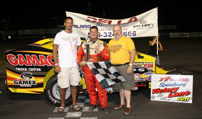 Modified winner Martin Roy, center, receives the winner's trophy from Della Auto Group at Airborne Speedway last weekend.