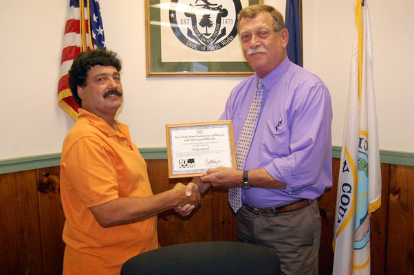 Mayor Gregory R. Martin, right, presents Larry L. Sorrell. superintendent of the village department of public works, with a framed certificate from the New York State Conference of Mayors and Municipal Officials. The organization recognized Sorrell for 25 years of service to the village.