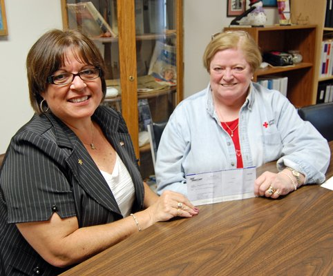 NBT Bank branch manager Sandy Walker, left, presents a check for $10,000 to Jeanie D. Roberts, executive director of the North Country Chapter of the American Red Cross. NBT Bank challenged the chapter to raise $10,000 during the month of June, which the bank then matched in its own donation.