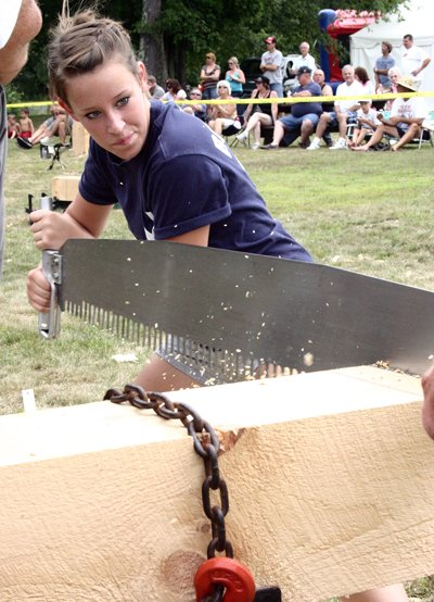 LUMBERJACKS & JILLS - Teamed up with her father Tim Keech of Bloomfield, Laura Keech of Bloomfield yanks on her end of a crosscut saw during a lumberjack competition held recently at the Stony Creek Mountain Festival.