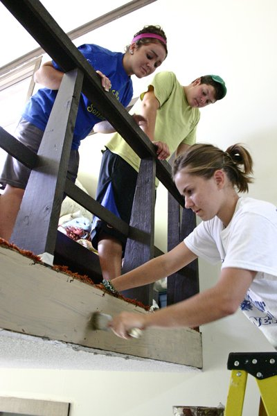 Effie Benz of the mission group YouthWorks paints  a landing recently at The Priory retreat in Chestertown while her fellow workers Madison Wiedehoeft (left rear) and Austin Maconty watch her progress. The three were among 700 teens who visited northern Warren County this summer, and worked as volunteers sprucing up churches, homes of the elderly and various municipal facilities.