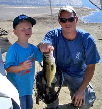 Shane Aikan, age 4, shows off the 2.4-pound largemouth base that netted him first place in the Schroon Lake Fishing Derby.