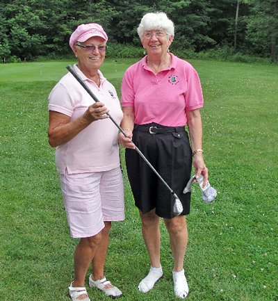 Arlene Davis, left is presented with a putter, her prize for closest to the pin, by Alice Leclerc, chair of Rally for a Cure.