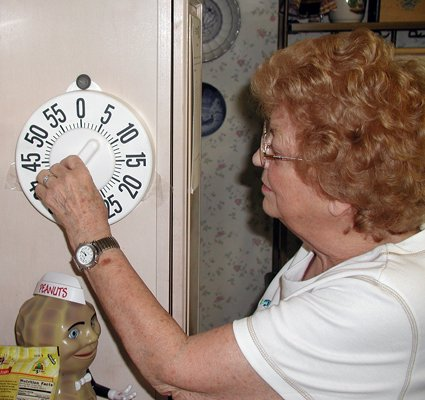 Millie Gellner, a resident of Lake Forest Senior Living Community in Plattsburgh, uses a low-vision timer, one of the several articles that may be recommended for people through the Courtesy Visit Program by the North Country Association for the Visually Impaired.