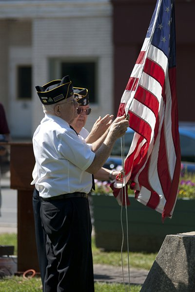 Members of American Legion Post 912, Rouses Point, raise new flags at Paquette Park on Main Street in the village of Champlain Aug. 20. A U.S. flag was donated by the post and a P.O.W. flag was donated by Woodmen of the World Lodge 462, Champlain.