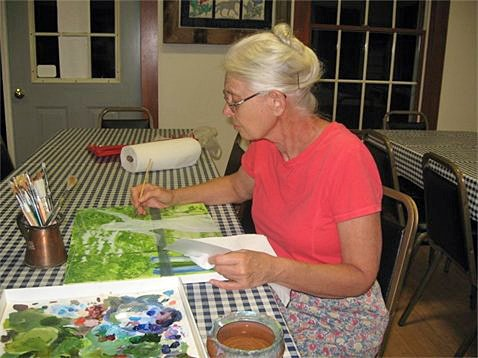 Watercolor artist Anne Rohe works on one of her landscape paintings recently. Adirondack Ambiance, the gallery that Anne operates with her husband Al, will be hosting a benefit show Friday, Aug. 26 and Saturday, Aug. 27 to raise funds for a local organization that helps families dealing with mitochondrial disease.