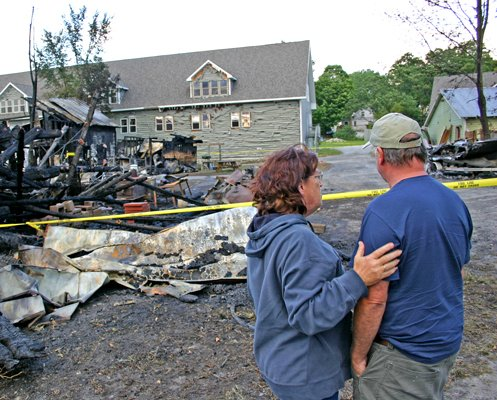Sally Wallace consoles Kent Duell as he surveys the damage caused by a fire Aug. 22 that destroyed three buildings and their contents in a River St. complex he and his wife Glenda own.