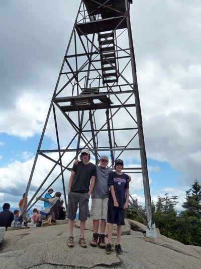 A crowd of hikers assemble in the shadow of the old firetower, atop Hurricane Mountain near Elizabethtown.