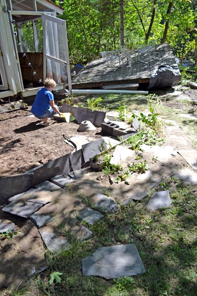 Elizabethtown resident Tris Horton sits on the foundation of her back yard deck, which was moved by flood waters against a line of trees along the banks of the Boquet River.