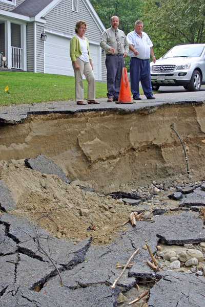 On a tour through Lake George inspecting damage caused by Tropical Storm Irene, state Sen. Betty Little (R-Queensbury), Lake George Village Public Works Superintendent Dave Harrington (center) and Lake George Town Supervisor FrankMcCoy gaze at a road washout carved by raging floodwaters careening through Scrimshaw Estates off Rte. 9N.