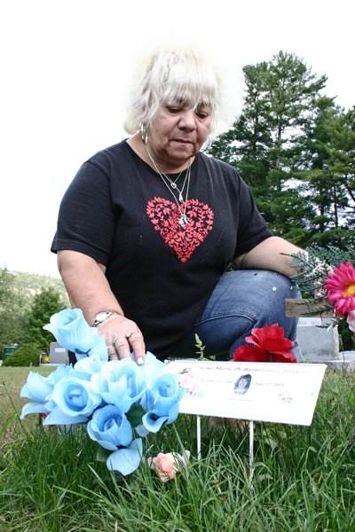 GRAVEVANDALISM  Alice DiBartolomeo of Warrensburg arranges flowers Sept. 12 on the grave of her daughter, Lisa Favaro, who was killed June 27 in an automobile crash. DiBartolomeo is upset because statues and solar lights have been stolen from Lisas grave, as well as from the burial plot of DiBartolomeos departed husband Anthony.  Local funeral director John Alexander said stealing items from graves was reprehensible. Its very unfortunate that some people have no respect, he said, noting that all local citizens must be vigilant and report any unusual activity in the towns cemeteries.