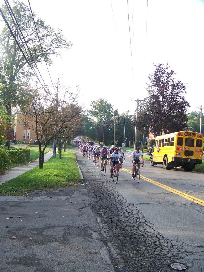 Bicyclists push themselves as they ride uphill through the village of Baldwinsville. The riders were participating in last Friday's Syracuse Ride for Missing Children.