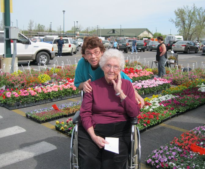 Volunteer MaryAnn Phillips accompanies Syracuse Home resident Doris Bushnell on a day trip in May to the Regional Market. Residents shopped for plants to fill containers on the grounds of the nursing home in Baldwinsville and spent the next week planting the flowers and vegetables that were purchased. This is the type of activity supported by the Syracuse Home Auxiliary, and proceeds from its upcoming arts and crafts festival will go to the Activities Program at Syracuse Home.