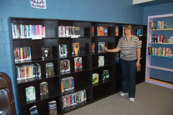 Laura Pritchard, director of the Dannemora Free Library, stands in the library's new location in the Village of Dannemora Office Building on outer Emmons Street. Pritchard said she's finally starting to feel settled into her new location about a month after the move.