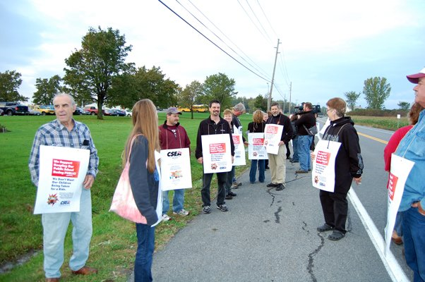 Parents, teachers, and union bus drivers and monitors wear picket signs outside Northeastern Clinton Central School board meeting Oct. 4.