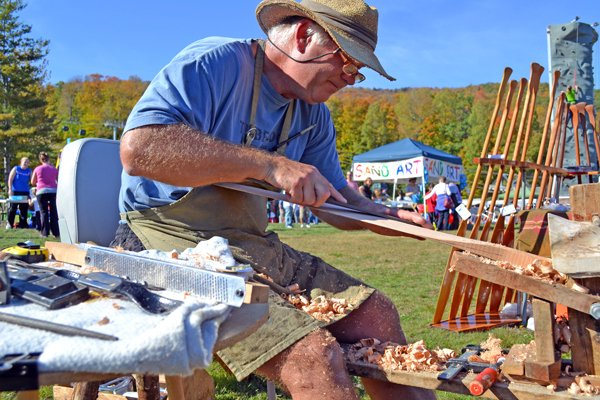 Caleb Davis carves an oar at Gore during the Harvest Fest Saturday. The festival features craftspeople who produce their own goods.