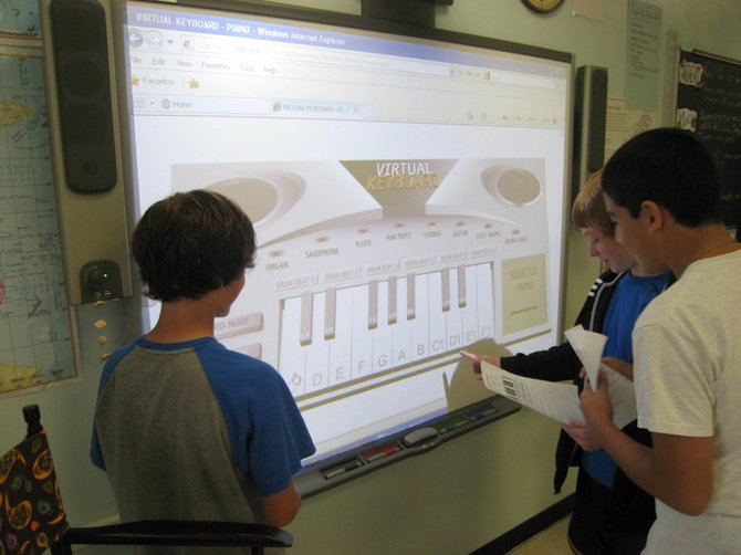 Thomas McKee, left, George Kresovich, center, and Jose Gomez, seventh-graders at Ray Middle School, use a virtual keyboard on the class SMART Board to play an original song they composed.