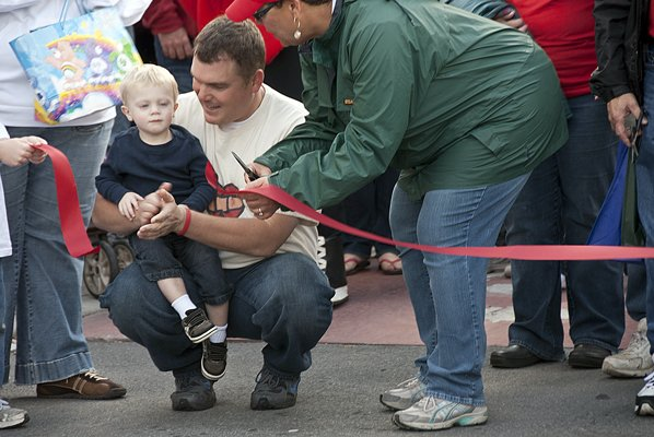 Heart defect survivor Luke Garcia and his father, Chad Garcia, assist stroke survivor Melody Trombly in cutting the ribbon during the American Heart Association's Plattsburgh Heart Walk last Saturday morning. Luke, 2, walked about one-quarter mile unassisted.