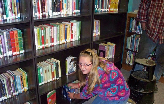 "Eleven-year-old Elizabeth Allen puts the final book on one of the shelves at the new home of Dannemora Free Library. Elizabeth won a contest which allowed her to pick the final book to be moved, choosing ""Winter of the Ice Wizard,"" by Mary Pope Osborne."