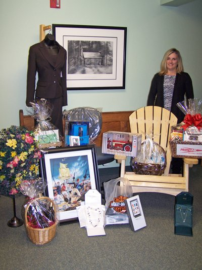 Becky Manor, with the North Country Chamber of Commerce, poses with items that will be up for auction at the chamber's annual Taste of the North Country event slated for Wednesday, Nov. 9. The event will once again be held at the Plattsburgh State Field House  on Rugar Street.