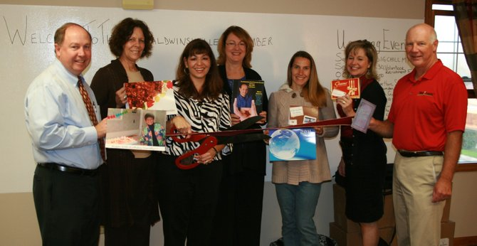 Karen Cannata-LaRocca, third from left, cuts the ribbon for the launch of her business Send Out Cards. She shared her new business in the Chamber of Commerce office for a before business hours open house and ribbon cutting on Oct. 11.