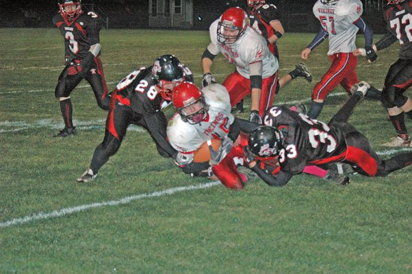 Tupper Lake defenders Clay Howard and Mitch Keniston gang up for a tackle on Moriah's Trevor Cheney.