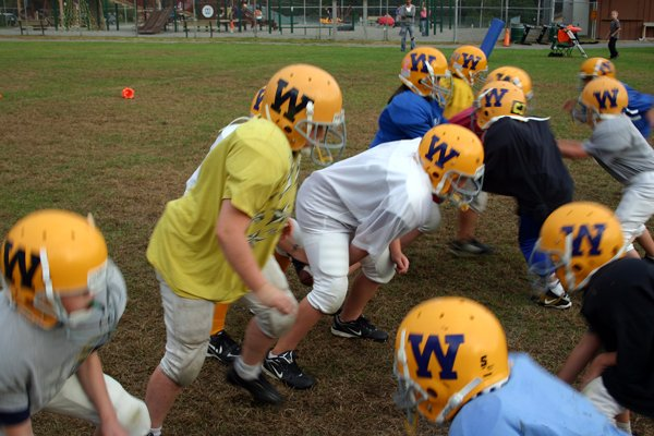 A squad of the Warrensburg Youth Football team jumps off the line of scrimmage in a recent practice session.