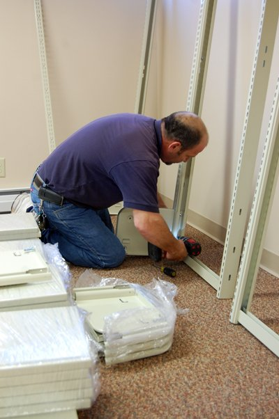 Lee Gilstrap of Library Interiors Inc., Brick, N.J., assembles shelving at the new location for the Chazy Public Library Tuesday morning.