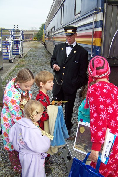 Saratoga & North Creek Railway Conductor Steve Conklin assists children as they board a passenger dome car Nov. 3 at the Saratoga Rail Station to celebrate the debut of the railway's holiday Polar Express excursion trips.