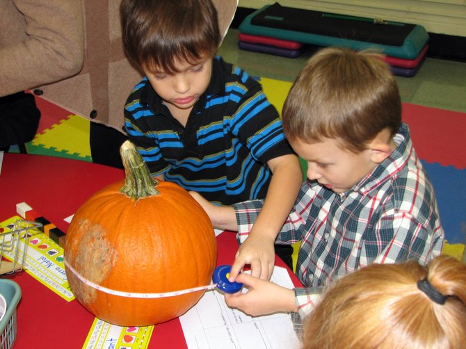Ben Lovell, left, and his classmate Joey Warner carefully measure their pumpkin's circumference.