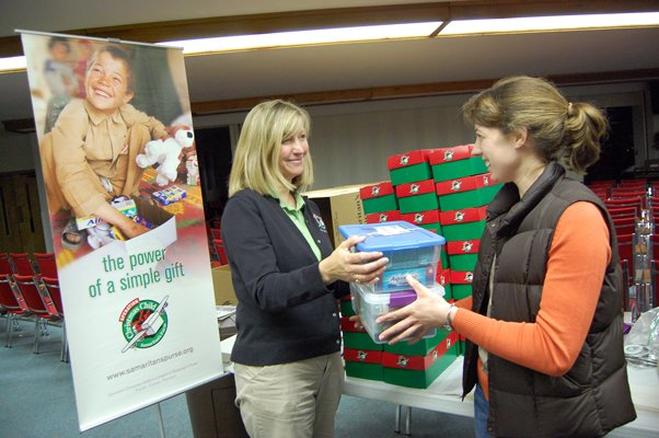 Anna Pape of Chazy, right, hands a shoe box of donated items to Rita Alford, coordinator for the Operation Christmas Child collection center at the First Assembly of God in Plattsburgh.
