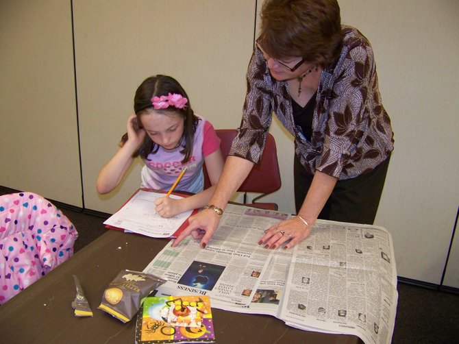 Celina Neugent, 9, receives assistance with her homework from Ellen Stevens of B'ville CARES during the newly created Kids Kount program held at the Baldwinsville Public Library.