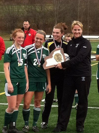 Chazy captains Kirsten Doran, Cailtyn LaPier and Katharine Tooke accept the NYSPHSAA Class D championship trophey along with head coach Karin Sherman Trombley.