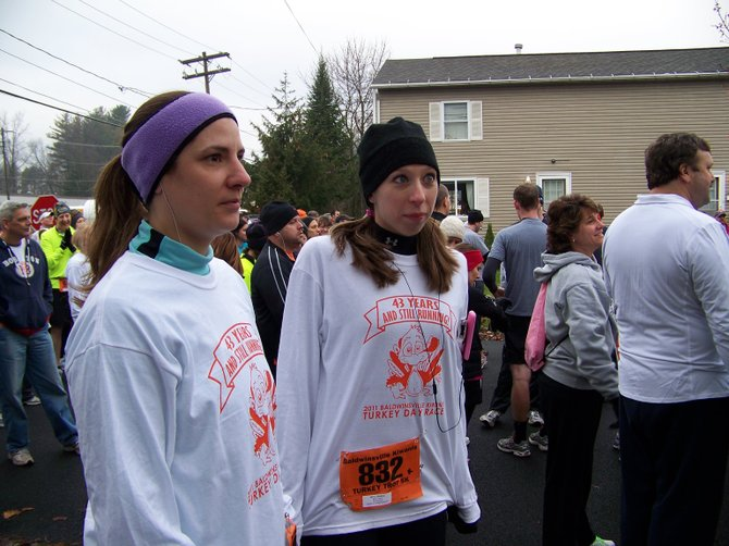 Lisa Depalma, of Syracuse, and Jessica Mirra, of Rochester, try to stay warm before running in the Thanksgiving Day 5K race, part of the 43rd annual Baldwinsville Kiwanis Turkey Day Race in the village.
