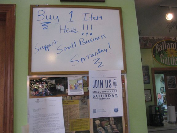 A sign at Ballentyne Gardens in Liverpool urges customers to buy goods at the local greenhouse on Small Business Saturday. Displayed below is a sign provided by American Express.