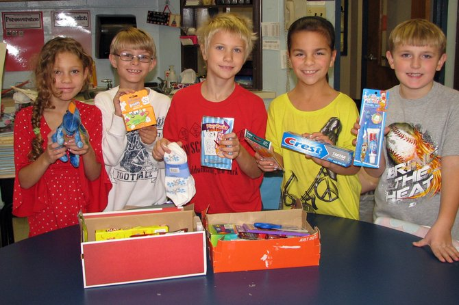 Van Buren Elementary School third-graders Margaret McClain, Griffin Gerharz, Jacob Neish, Kelsey Natoli and Eric Hildreth display the items they collected to send to children around the world through Operation Christmas Child.