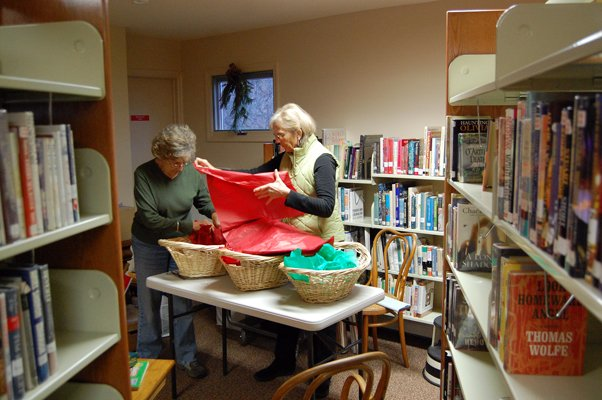 Carol Ladd (left) and Ann Maynard of Friends of the Library make baskets that will be raffled at the Chazy Public Library's grand opening Saturday.