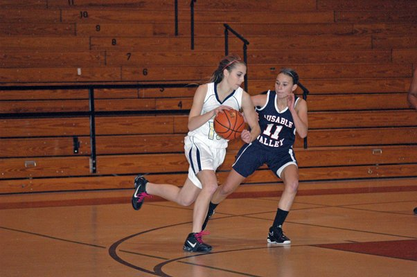 Lake Placid's Danielle Balestrini tries to drive to the basket against Cammey Keyser of AuSable Valley. The Lady Patriots beat the Lady Blue Bombers 50-30 in the opening game of the Coaches v. Cancer CVAC Challenge.