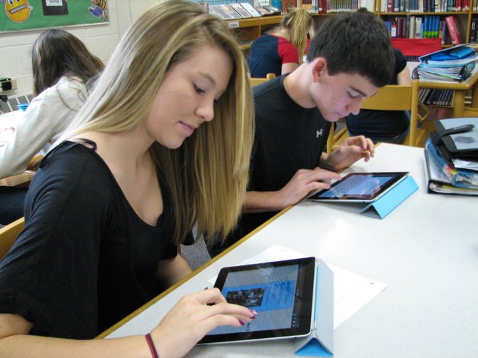 Hannah Wood, left, and her classmate Jonathan Dunn use iPads in the school library to gather information for a research project at Durgee Junior High School.