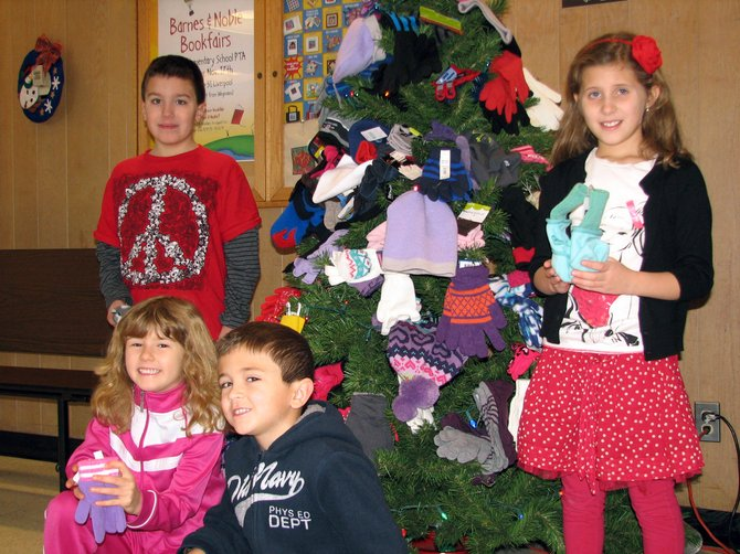 Korben Haney, left, Allie Cavino, Daniel Nadelen, and Ava Pompo pose in front of the tree that Palmer Elementary School decorated with hats and mittens students collected to donate to the Baldwinsville Christmas Bureau.