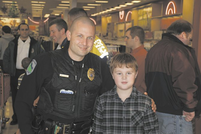 Hunter Gasque, 10, right, was one of the winners of the Cicero Police Department's Shop with a Cop contest. He chose to spend his $100 Target gift card on gifts for the seniors served by North Area Meals on Wheels.