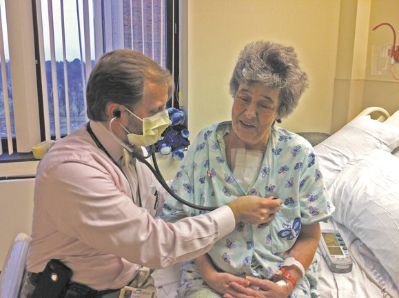 Dr. Eugene Storozynsky listens to Carol Kankoski's new heart beating strongly in her chest.  Surgeons at University of Rochester Medical Center performed a heart transplant on her Dec. 15. There are more than 800 people in the area awaiting new organs.