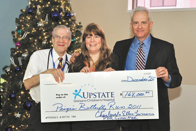 Richard Sills, MD, professor of pediatrics and chief of pediatric hematology/oncology at the Upstate Golisano Children's Hospital, accepts a $168,000 donation from Ellen Yeomens and Chris Arnold of Baldwinsville, founders of Paige's Butterfly Run, of which the proceeds were raised from in 2011.