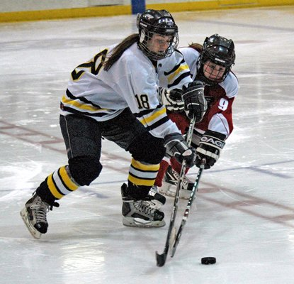 Lake Placid girls varsity hockey player Brooke Reid (18) tries to get control of the puck against Beekmantowns  Amanda Kempainen during their Jan. 9 game at the 1932 Rink at the Lake Placid Olympic Center.