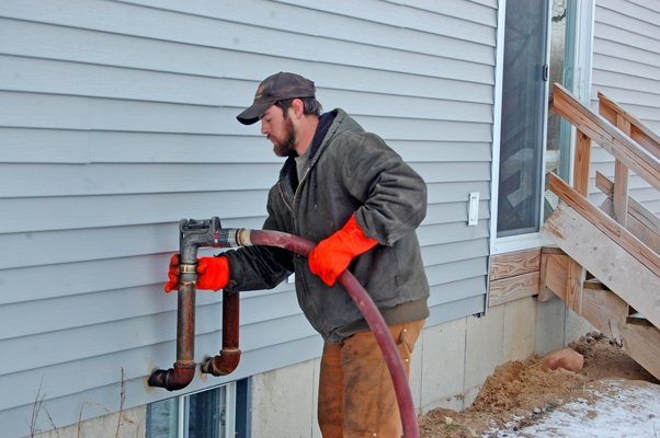 Josh Leroux, co-owner of Leroux Fuels in Plattsburgh, delivers home-heating fuel to a residence on Surrey Drive in West Chazy.