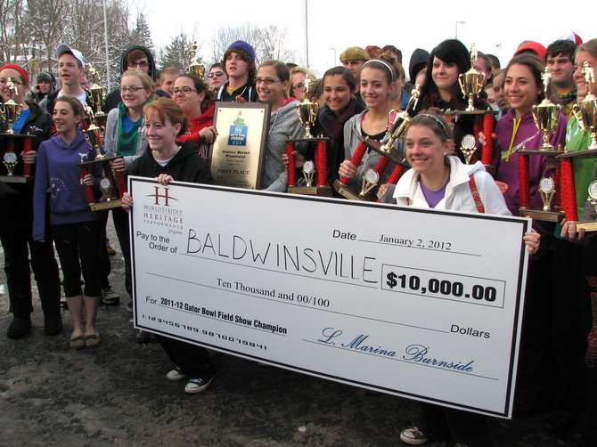 Members of the Baldwinsville Marching Band display the many trophies and the $10,000 check the band was awarded at the Gator Bowl.