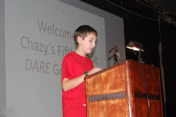 Justin Collins, a Chazy Central Rural School fifth grader, reads from his essay at the DARE graduation.