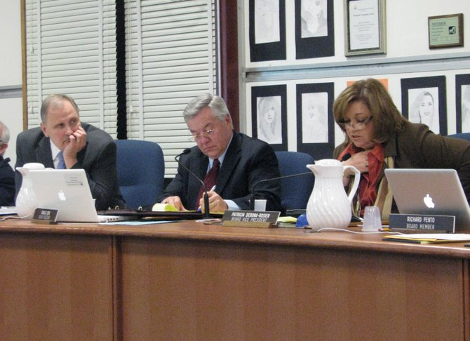 Liverpool Superintendent Dr. Richard Johns, left, listens as school board member Pat DeBona-Rosier speaks during a board of education meeting Monday Jan. 23. Between them is board president Don Cook.